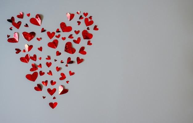 흰색 배경에 고립 된 하나의 큰 마음을 형성하는 많은 빨간색 작은 마음의 배경