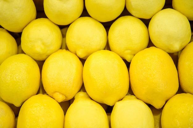 市場や店のカウンターに多くの黄色いレモンの背景