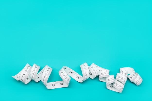 청록색 배경에 절연 측정 테이프의 배경. 체중 감량, 다이어트, 과체중 개념
