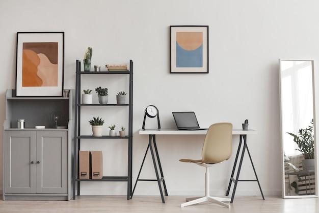 Фон минимального рабочего места домашнего офиса в современной квартире, украшенной растениями и абстрактным искусством, копией пространства