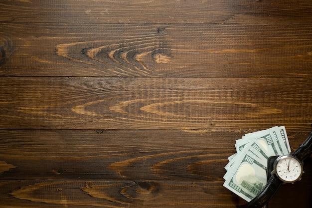 お金と木製の机の上に横たわる時計の背景。時間の概念はお金です