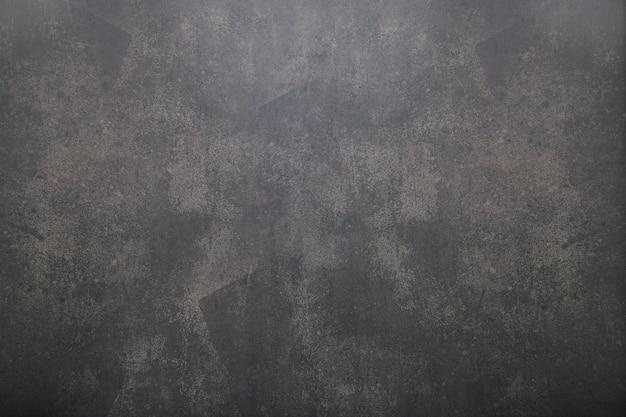 Предпосылка старого состаренного грубого темного покрашенного бетона с текстурой пятен. вид сверху винтажной темной конкретной предпосылки.