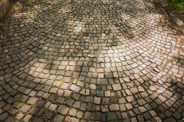 Фон из старой брусчатки на улице в свете солнца