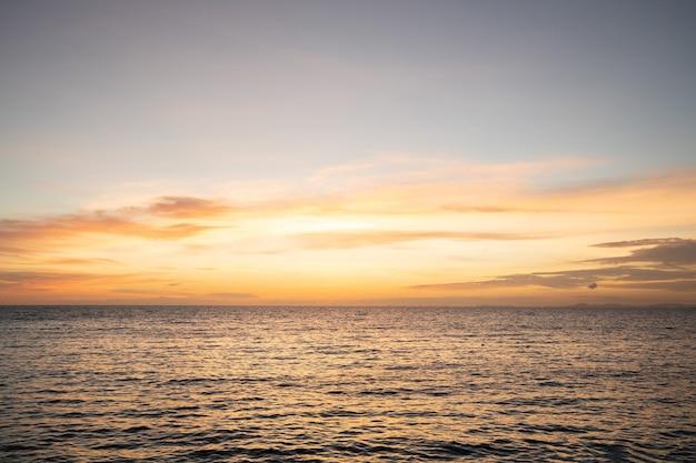 海に向かってオレンジ色の夕暮れの夕焼け空の背景