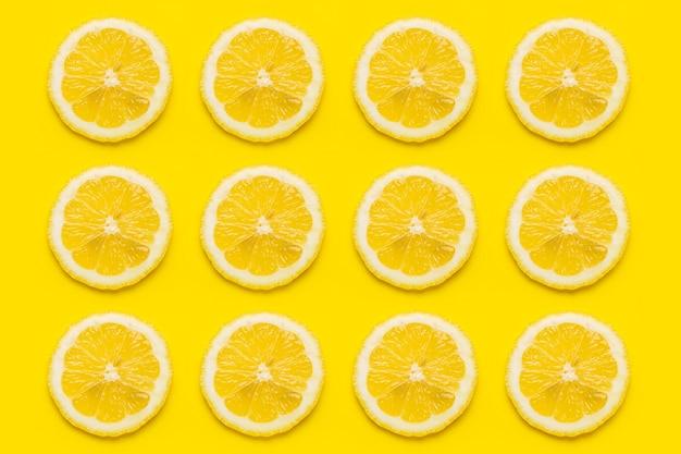 노란색 표면에 익은 레몬 조각의 배경. 평면도, 평면도.
