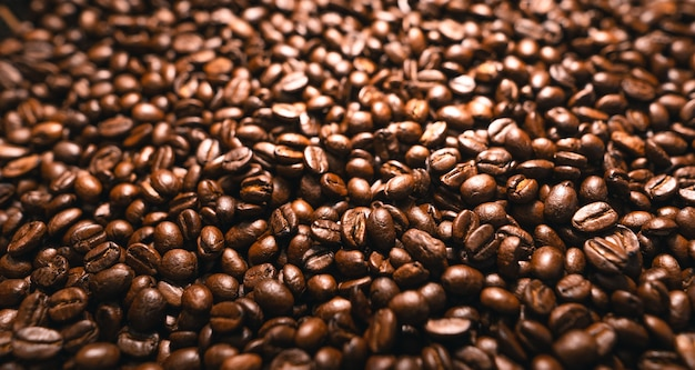 Фон из жареных свежих коричневых кофейных зерен, крупным планом выстрел из свежих кофейных зерен кофе текстуры