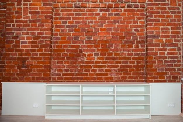 部屋の背景は、装飾的な赤レンガの壁と家具を備えたロフトスタイルでデザインされています。装飾的な要素を持つグランジインテリアの工業デザイン。テキストの著作権スペース
