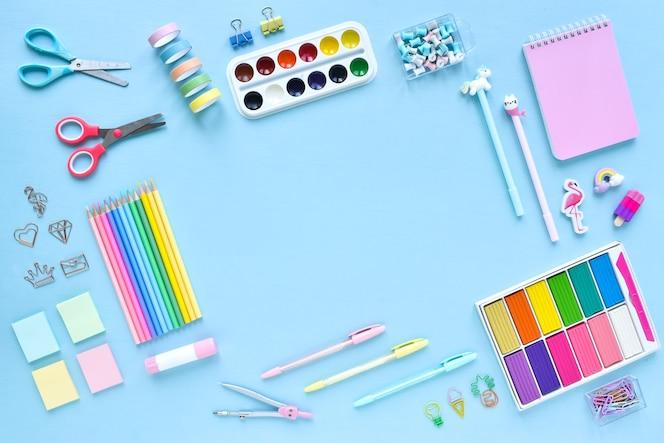 밝은 파란색 배경, 텍스트 공간에 파스텔 색상의 학교 용품의 배경. 사무용품. 학교로 돌아가다. 그것은 평평했다.