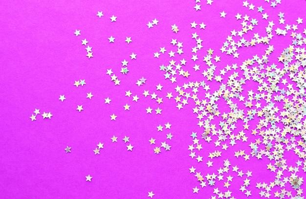 Фон из блестящих маленьких звезд на ярко-розовом фоне. рождественское понятие. текстура блеска.