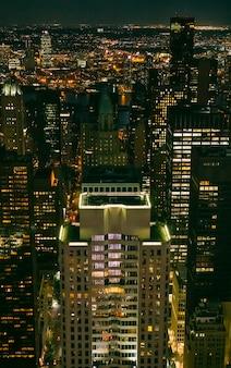 ニューヨーク市マンハッタンの夜に照らされた高層ビルの窓の背景