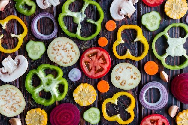 Фон нарезанные свежие овощи на деревянном фоне