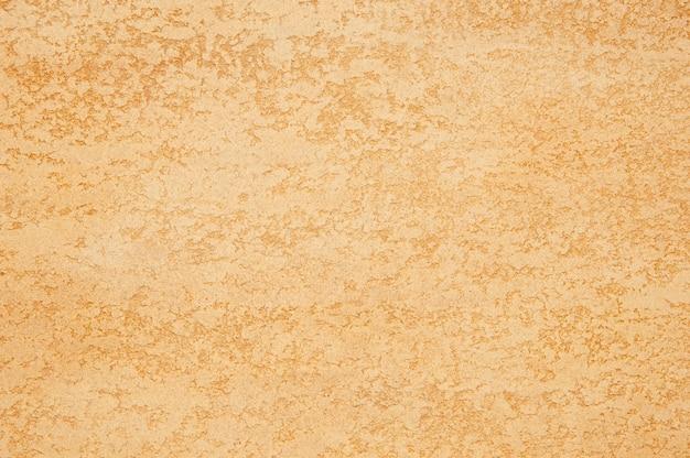 황금 색상의 질감된 석고의 배경입니다. 예술 배경