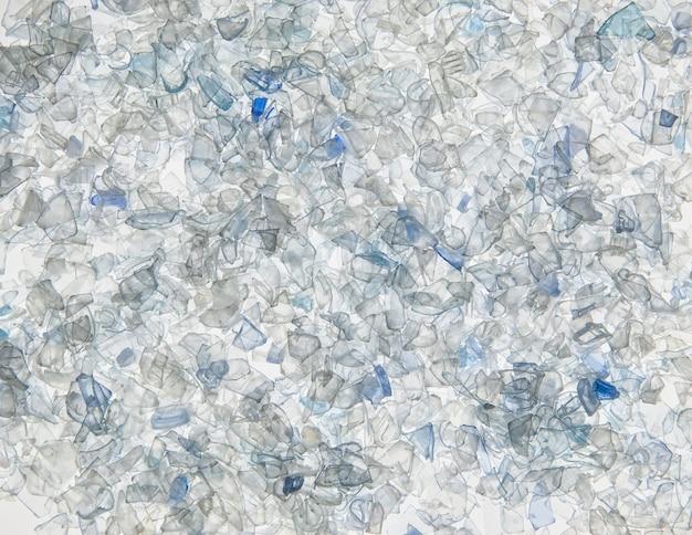 Фон из кусочков пластиковых бутылок белого и серого цвета. нарезанные кусочки пэт бутылок