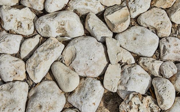 다양한 모양과 크기와 질감의 돌로 만들어진 성의 돌담 배경.