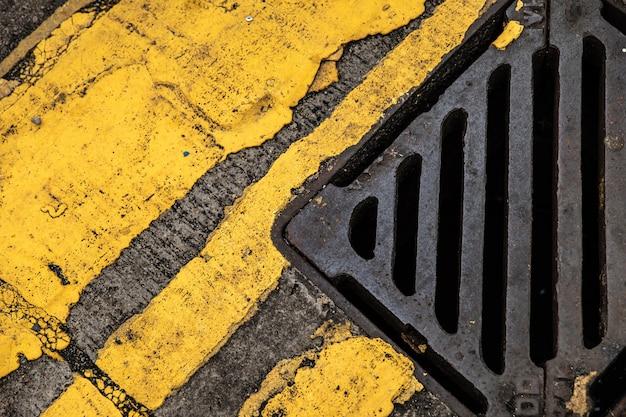 古いアスファルトの雨水管と黄色い道路標示の背景