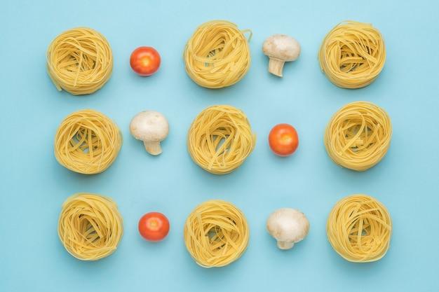 Фон из помидоров, грибов и скрученных макарон на синем фоне