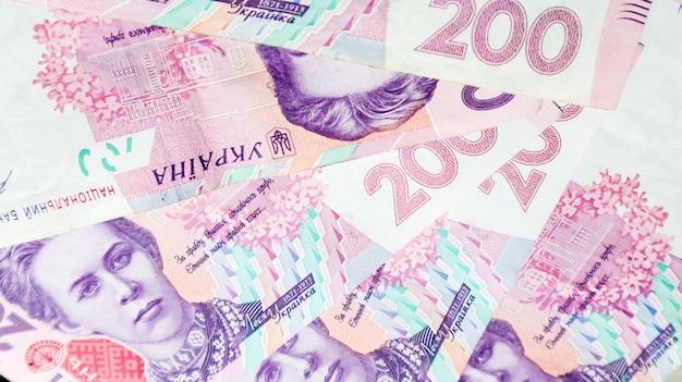 Фон украинских банкнот номиналом 200 гривен. много денег. вид сверху. гривна - национальная валюта в украине.