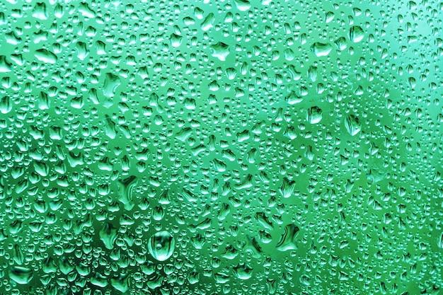 Фон капель воды на окне после летнего дождя с зеленой листвой за стеклом