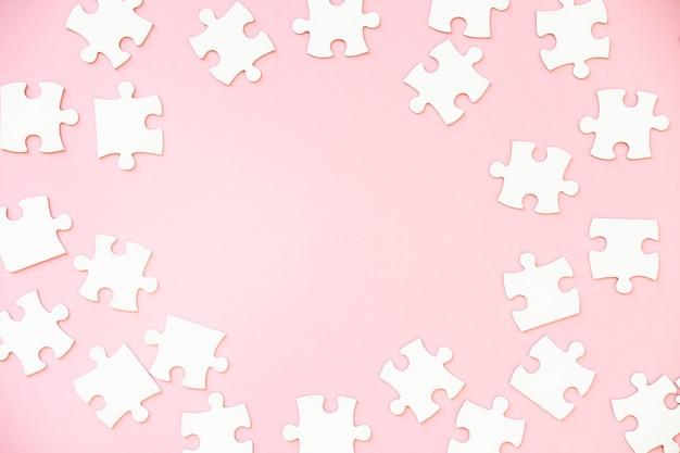 ピンクの白いジグソーパズルのピースの背景、上面図