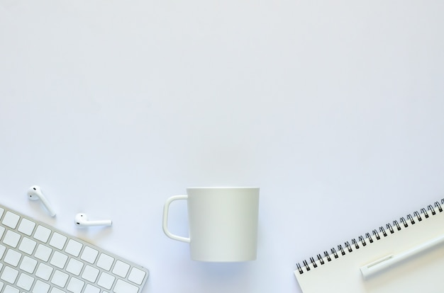 白い背景の上のコーヒーカップとオフィスの文房具とワークスペースコンセプトの背景。