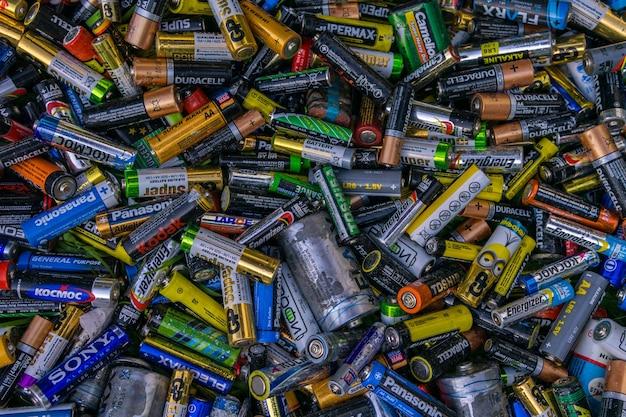 Фон старые использованные выброшенные элементы aa и другие электрические батареи