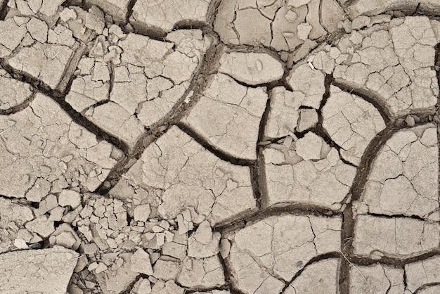 灰色のひびの入った汚れた乾燥した地球または地面の背景またはテクスチャ