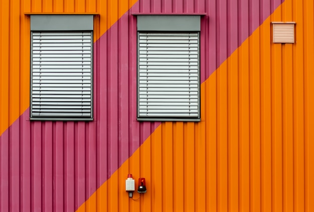Background of an orange and purple metal wall with white window blinders