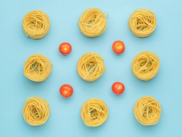 Background of pasta and fresh tomatoes on a blue background.