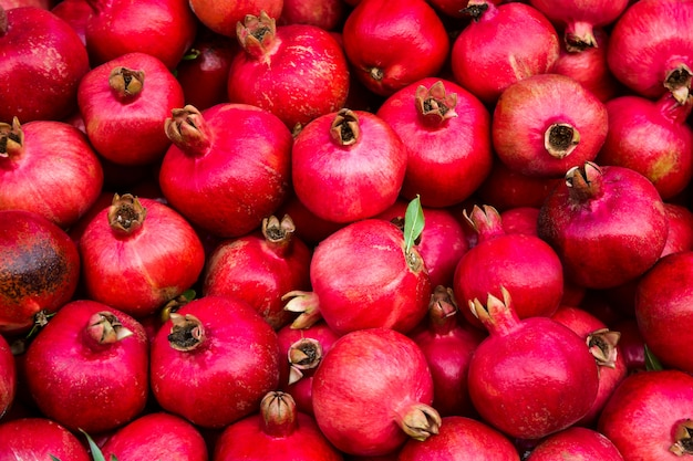 Background pattern of red ripe pomegranates in dark colors