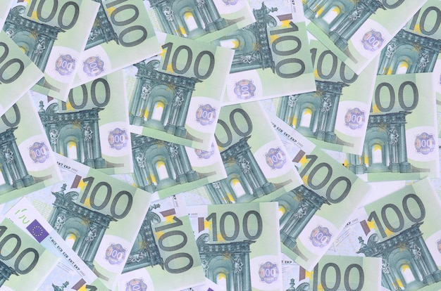 Background pattern of a set of green monetary denominations of 100 euros. a lot of money forms an infinite heap