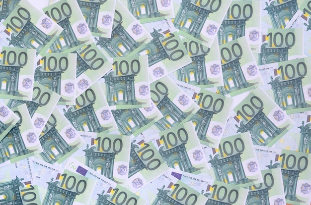 Background pattern of a set of green monetary denominations of 100 euros