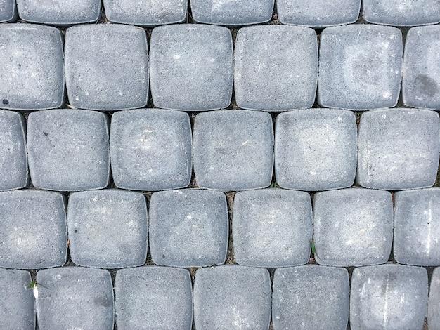 Фоновая тротуарная плитка. цементно-кирпичный пол. променад, вид сверху. абстрактная текстура - серая тротуарная плитка в виде квадратов. серый квадратный тротуар. бесшовные текстуры с наклоном. место для текста или логотипа