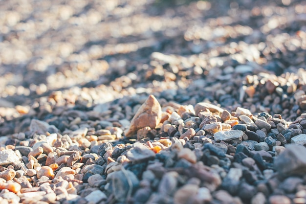 Background of pebbles stones with shadows, selective focus