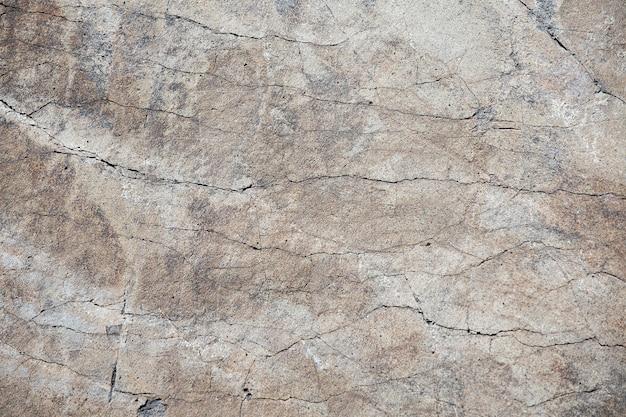 Фоновое фото текстуры разбитой и поврежденной поверхности стены сероватых тонов.