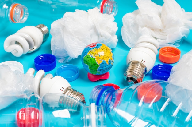Background of plastic bottles of transparent, plastic bags, fluorescent, globe. flat lay