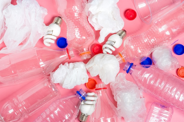 Background of  plastic bottles of transparent, plastic bags, fluorescent, globe flat lay