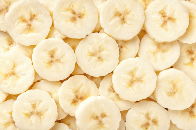 Background of ripe sliced banana slices, closeup.