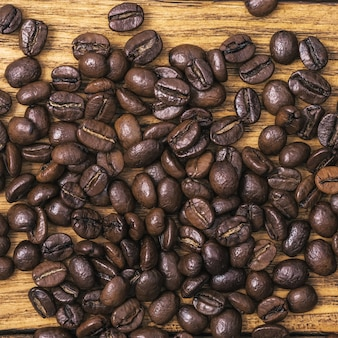 Background of roasted coffee beans is brown on wooden boards