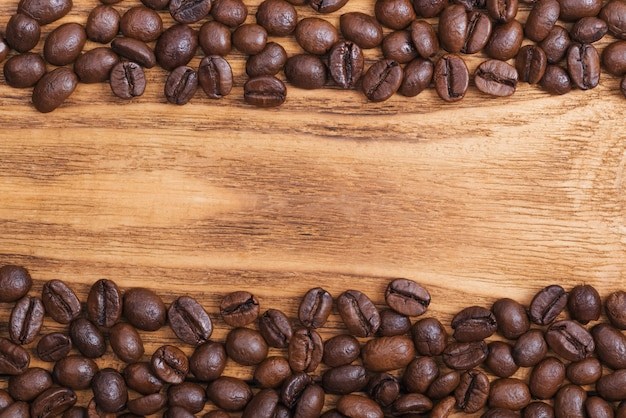 The background of roasted coffee beans is brown on wooden boards