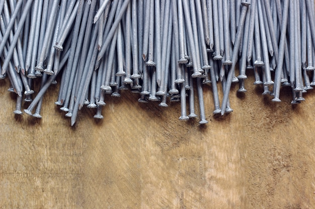 Background of roofing nails on a wooden platform