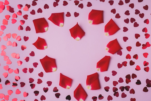 Background of rose petals and red hearts.