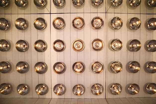 Background of round lamps on a wooden wall, reflected repeatedly in the mirrors
