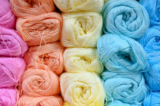 Background of rows skeins of thin fluffy wool yarn for knitting different pastel colors. soft light color of pink, orange, yellow, mint and blue