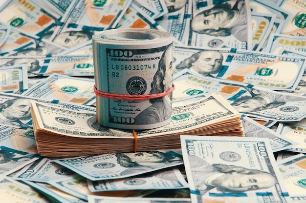 A background of scattered one-hundred-dollar bills
