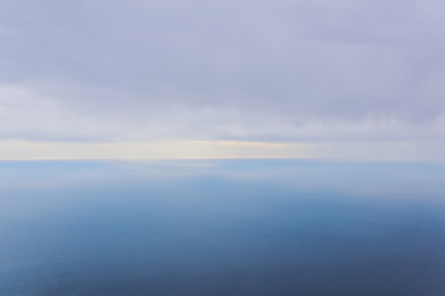 Background, seascape - clouds and rains over the foggy winter sea, top view
