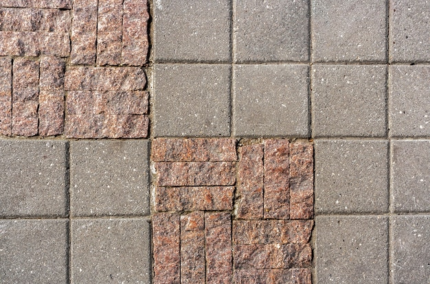 Background of stone tiles in different size and facture on  sidewalk.