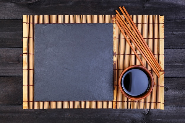 Background for sushi. bamboo mat and soy sauce on black wooden table. top view and copy space