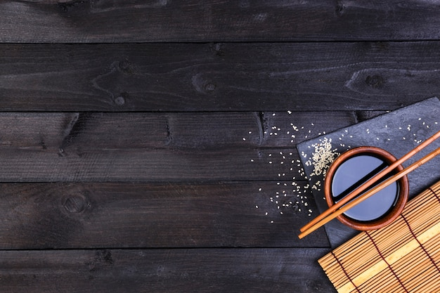 Background for sushi. bamboo mat and soy sauce on black wooden table. top view with copy space