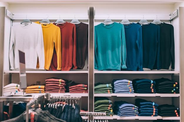 배경. 스웨터는 슈퍼마켓 진열장의 옷걸이에 걸려 있습니다.