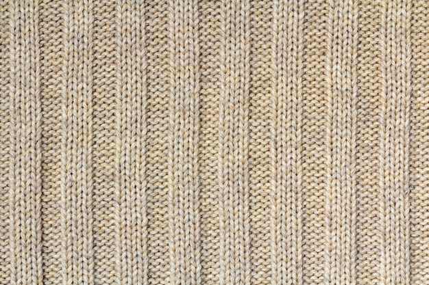 Background texture of beige pattern knitted fabric made of cotton or wool closeup